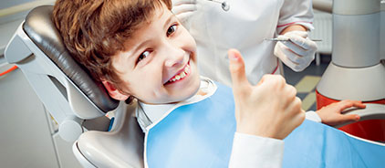 Child giving the thumbs-up in a dental chair after a visit to pediatric dental office Total Dentistry in Palantine, IL