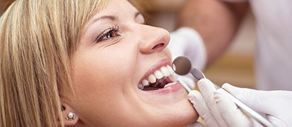 Woman sitting in a dental chair while the dentist examines her teeth at Total Dentistry in Palantine, IL