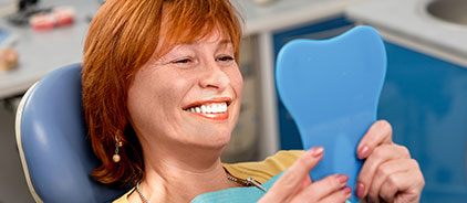 Woman examining her smile in a mirror after receiving dental implants at Total Dentistry in Palatine, IL